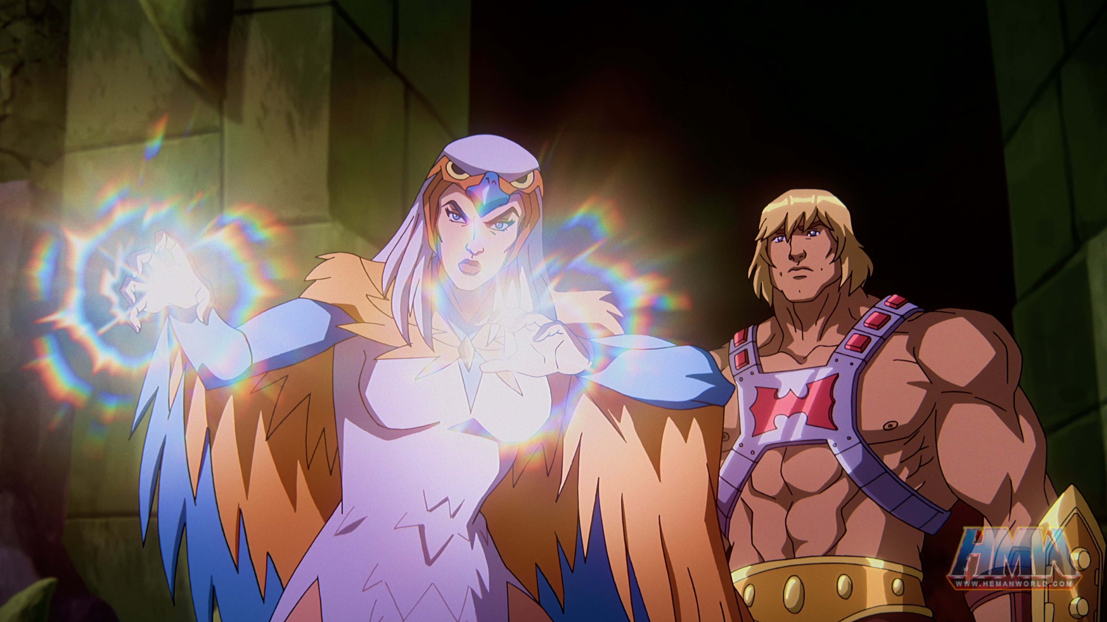"""In a CG animated still from Masters of the Universe: Revelation, He-Man (right) stands behind Sorceress (left) in a stone room lit only by the light coming from Sorceresses' hands. Sorceress has her palms outstretched in front of her and wears a white dress, a falcon-like hood over head and orange and blue wings. He-Man wears a silver chest plate with a red """"H"""" in the center, a golden armored belt and wrist plates."""